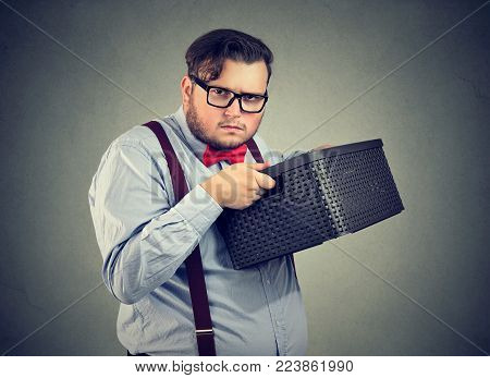 Unsociable man holding box and looking unwilling to share while posing on gray.