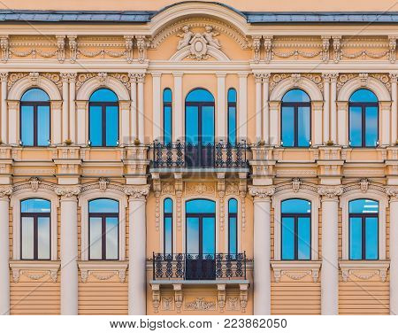 Several windows in a row and balconies on the facade of the urban historic building front view, Saint Petersburg, Russia