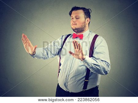 Blindfolded chubby man with eyes closed touching air.