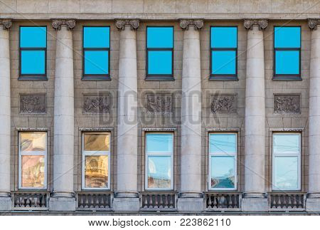 Several windows and columns in a row on the facade of the urban historic building front view, Saint Petersburg, Russia