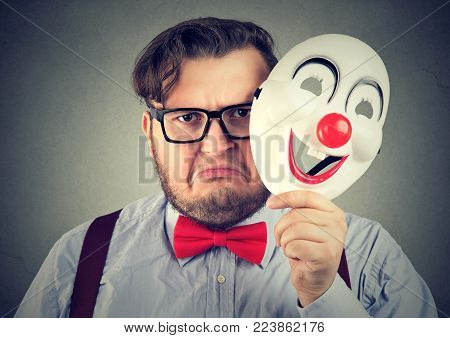 Young upset man frowning while looking at camera and holding happy clown mask.