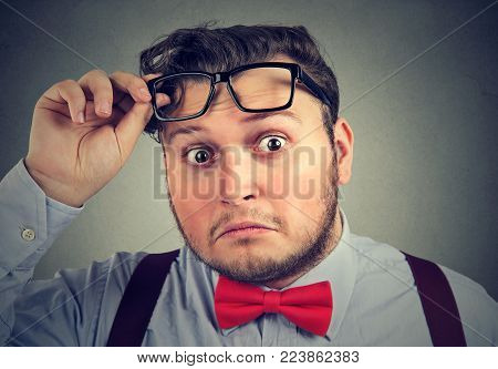 Young chubby man taking off glasses and looking at camera with big surprise.