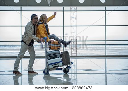 Joyful start of journey. Profile of happy young couple is having fun in terminal lounge. Man is pushing airport trolley with suitcases and his cheerful girlfriend who is sitting on it. Copy space
