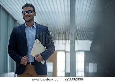 Success and confidence. Portrait of optimistic young stylish man is standing with folder and looking ahead with smile. Copy space in the right side