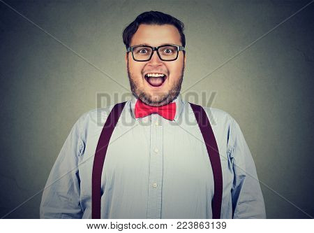 Obese man wearing eyeglasses and red bow-tie looking at camera looking impressed.