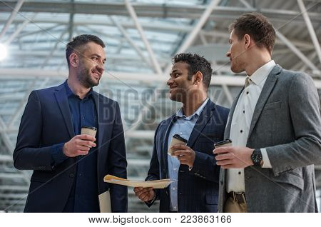 Get some energy. Optimistic young stylish men are drinking fresh espresso and holding papers while exchanging new ideas