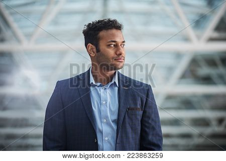 Feeling self-assured. Elegant stylish young businessman is standing and looking aside confidently