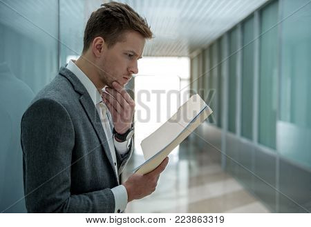 Busy morning. Pensive young professional employee is reading documents with concentration. He is standing in hallway and touching his chin. Copy space in the right side
