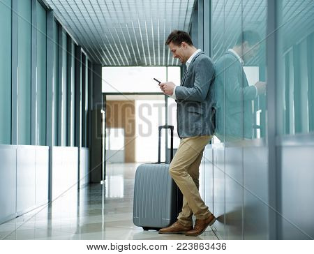 Useful device. Full length of charming young optimistic traveler with luggage is leaning on wall while holding mobile phone and smiling. Copy space in the left side