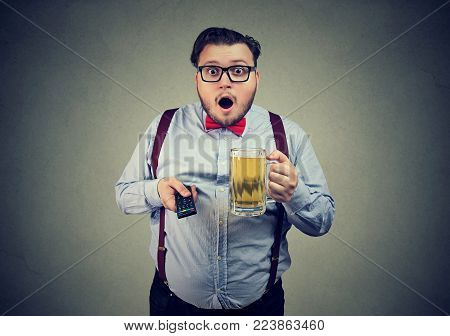 Chubby man holding mug of beer while watching TV and looking amazed.