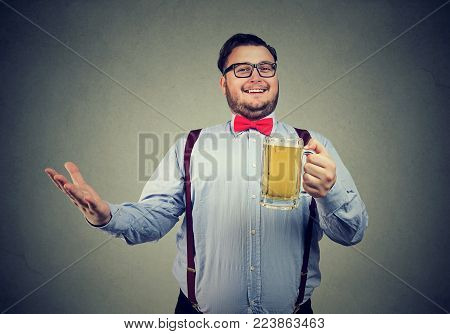 Chunky man in formal outfit and eyeglasses posing happily at camera holding mug of beer.