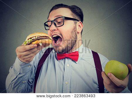 Chubby man in eyeglasses eating burger choosing junk food instead of healthy diet.