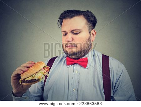 Young obese man looking at burger with disgust dissatisfied with fast food quality.