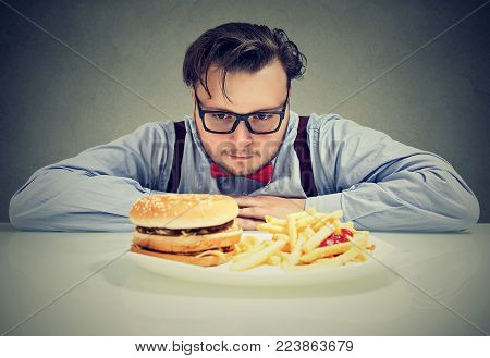 Young chunky man in eyeglasses craving cheeseburger with fries looking stressed while being on diet.