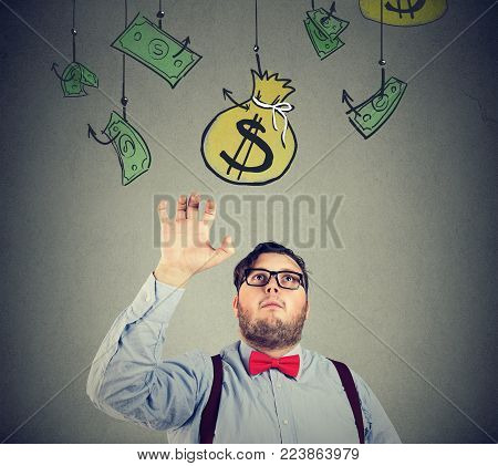Chunky man in formal clothing grabbing sack of money conducting business.
