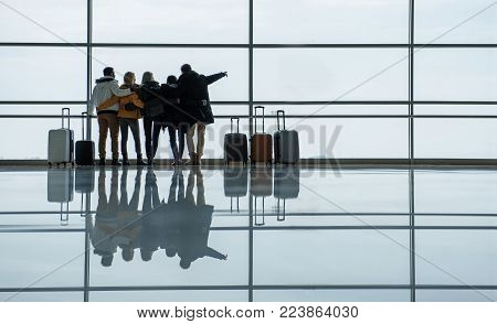 Best friends. Full length back view of travelers are standing together with luggage and hugging at international airport. They are looking through the window while waiting for flight. Copy space