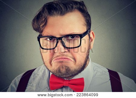 Portrait of chunky man in eyeglasses looking offended and gloomy posing at camera.