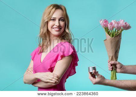 Will you marry me. Portrait of happy young woman is standing and smiling. Male arms is holding ring box and flowers near her. Isolated