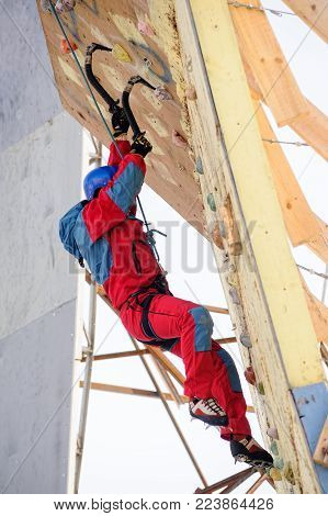 Tyumen, Russia - March 31, 2012: Rock climbing wall of Alkor club. Ice climbing competition. Man climbs upward on surface with negative inclination