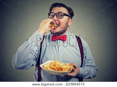 Young chubby man holding plate and devouring crispy potato chips.