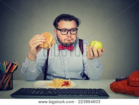 Chubby man looking confused and sad trying to choose between apple and burger while spending time in office.