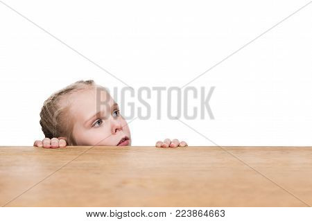 Little beautiful girl holds hands at table and peeks out for him isolated on white background