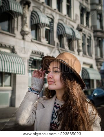 Portrait of a young female tourist with elegant hat and coat exploring the city. Trendy woman traveler with smile touring old town. Beautiful girl walks in  Rotterdam, Netherlands.