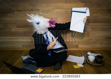 Young man in comical rubber mask sits on the floor against a wall with a lot of gadgets around him. Unicorn in a suit and tie smiles and shows a white empty sheet with copy space. Any text possible.