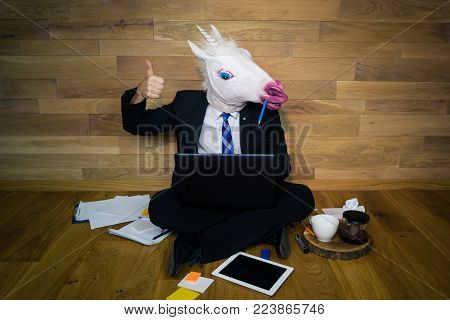 Work is done! Young man in funny rubber mask sits on the floor against a wall and works in laptop with a lot of gadgets around him. Unicorn in a suit and tie smiles and shows thumb up.