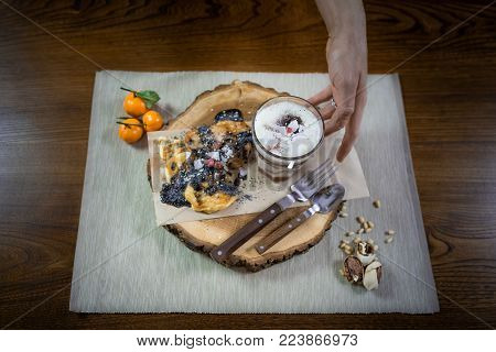Beautiful dish for breakfast on the stylish wooden tray. Fresh protein pancakes and parfait with fruits decorated with toppings and nuts on the wooden table. Final touch. Ready to eat. Close up view.