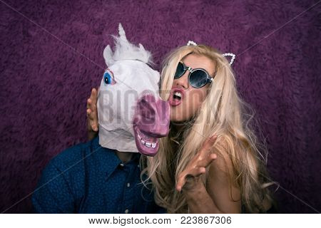 Portrait of happy unicorn in the arms of freaky young woman in sunglass and kitty ears on the purple background. Expressive blond with strange guy. Unusual people shows emotions.