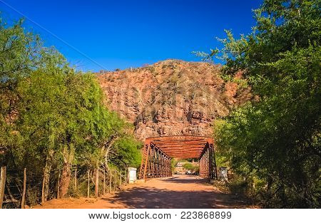 Old steel bridge construction over a river leading to  the small village Alemania, northern Argentina