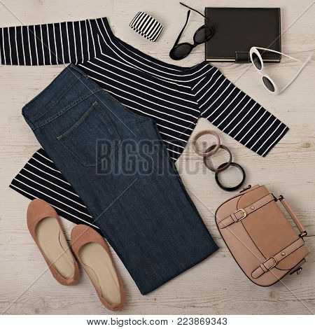 Female summer outfit - navy jeans, striped top, sunglasses, backpack. Selective focus.