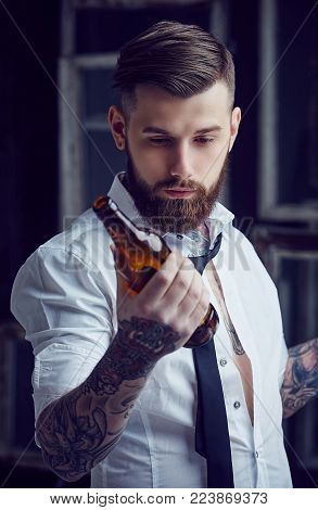 Bearded tattooed man in white shirt drinking beer.