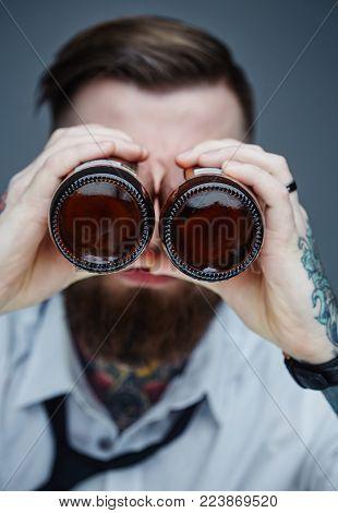 Bearded tattooed man holding beer bottle like monocular.
