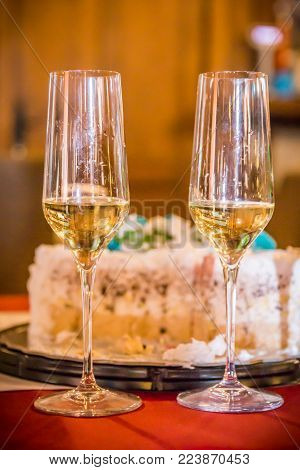 Two champagne glasses with cake on the restaurant table. Romantic wedding party at night. Celebration event. Close up.