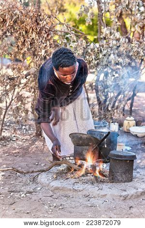 African woman cooking outdoors kitchen in the village, Botswana