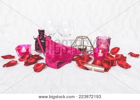 Valentines Day concept. Pink g-strings with wine glasses, roses and candles on white textured background. Isolated.