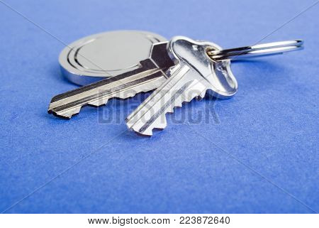 Set of silver coloured house keys on blue texture background. Shallow DOF, focus on end of second key. These are used house keys with a few scratches. Lots of copy space.