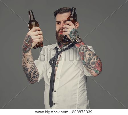 A man in white shirt with tattooes on his arms holding two beer botles. Isolated on grey background.