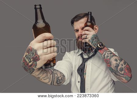 Tattooed man in white shirt holds two bear bottles. Isolated on grey background