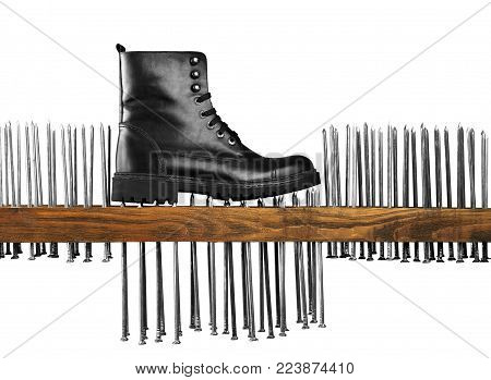 Black male boot made of leather. A boot stands on nails and a wooden board on a white background