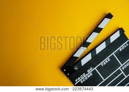 Cinema minimal concept. Watching film in the cinema. clapper board on yellow background. Screenwrite desktop