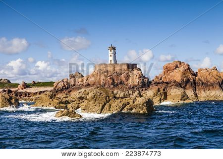 Lighthouse on the Ile de Brehat, on the Pink Granite Coast, Brittany, France, seen from the sea.