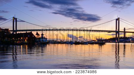 This is a suspension bridge in Gothenburg, Lnadmark of swedish architecture. Shot from boat during blue hour. Setting sun creating beautiful colors.