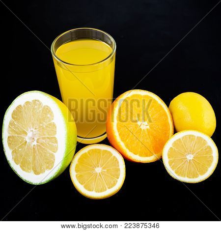 Juice with lemon, orange, mandarin, and sweetie on black background. Flat lay, top view. Fruit background