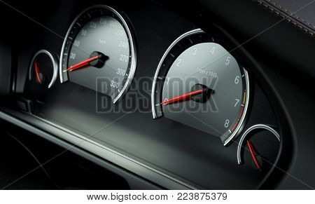Close  up shot of a speedometer and tahometer in a car.