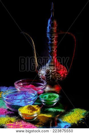 Indian Holi festival colours. Several bowls with Holi paint powder. Indian lipped jug on black background.