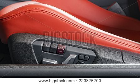 Red leather driver seat with stitching inside luxury car interior, power seat control buttons