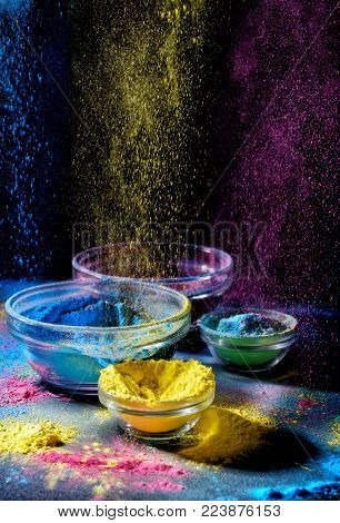 Indian Holi festival colours. Several bowls with Holi paint powder. Explosion of purple, yellow and blue color on black background.